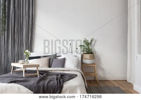 Interior of white and gray cozy bedroom with coffee on a tray
