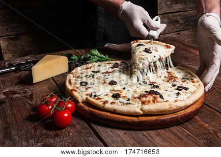 Chef lifting slice of hot tasty pizza with melting cheese on rustic wooden table. Italian cuisine, fast food.