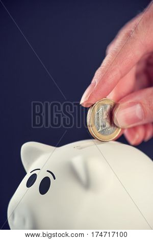 Woman putting one euro coin in piggy bank money savings and home budget concept