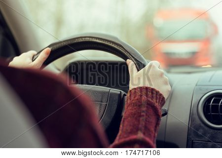 Woman driving car toward a large truck on the road selective focus on hands gripping the steering wheel of the vehicle retro toned image