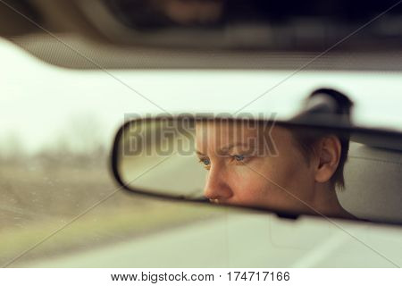 Reflection of female face in car rearview mirror while overtaking someone on open road retro toned