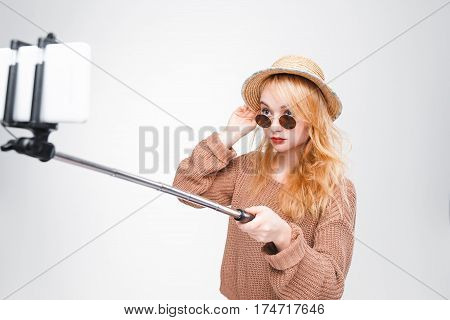 Young girl in sunglasses and straw hat takes photo with selfie stick. Fashionable hipster girl having fun. Fashion blogger. Grey background with copy space.