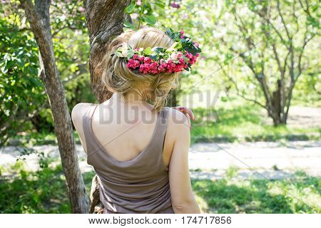 Slim young blonde girl in a brown sundress and a wreath of roses