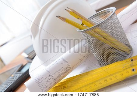 Construction plans with helmet and drawing tools on blueprints with calculator in a background