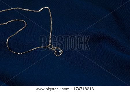 Golden chain with pendant in form of heart on the deep blue background