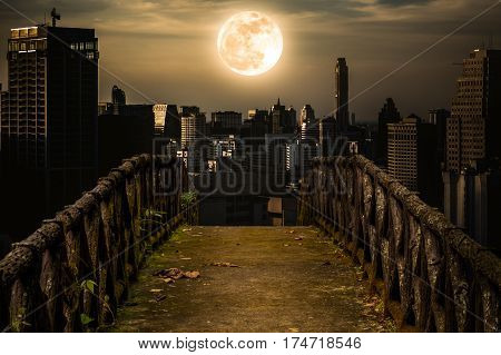 Old concrete bridge with wooden across to skyscrapers with super moon background at night. Dark tone and high contrast style. Sepia tone. The moon were NOT furnished by NASA.