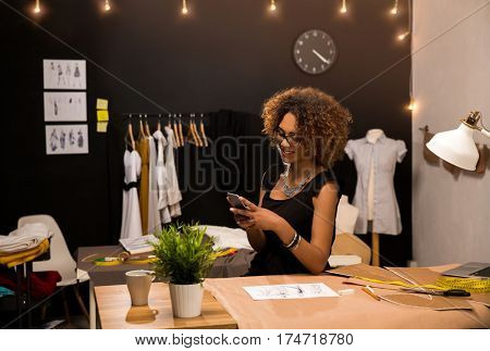A young fashion designer on her atelier making a phone call