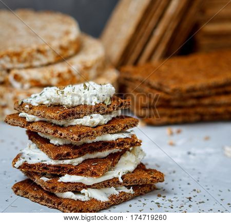 Sandwiches with curd cheese and bread roll for breakfast on a background stacks of various healthy crisp bread diet vitamin snack.