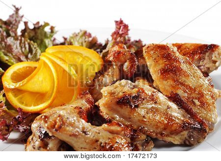 Grill Chi?ken on a Plate with Leaf of Salad and Slice Orange. Isolated over White