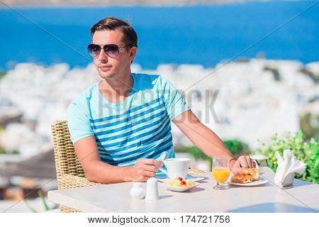 Young guy having breakfast at outdoor cafe with amazing view on Mykonos town. Man drinking hot coffee on luxury hotel terrace with sea view at resort restaurant.