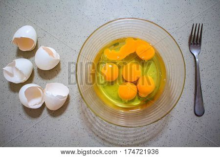 Cooking of eggs in glass bow. Healthy breakfast protein ingredient. Scrambled eggs preparation. Broken eggshells on table. Transparent and yellow content of raw eggs. Nutritional omelette cooking