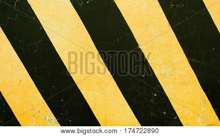 Dangerous road sign. Black and yellow stripes on concrete block texture. Dangerous way concept. Serpentine roadside stop. Danger on highway. Safe drive reminder. Yellow black paint on rough texture