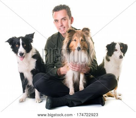 three dogs and man in front of white background