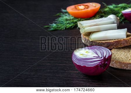 lard (salo) with bread with red onions on the background of the tomato with garlic dill on wooden table.