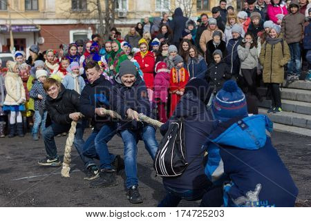 Marganets, Ukraine - Fabuary, 26: Young boys are dragging rope in front of crowd while celebrating Slavic family holiday Maslenitsa on 26, Febuary, 2017 in Marganets, Ukraine