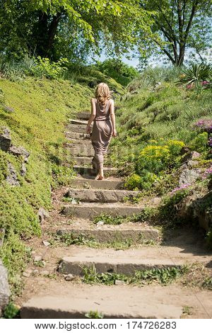 Slim young blonde girl in a brown sundress climbs up the stairs in the park. Sumertime.