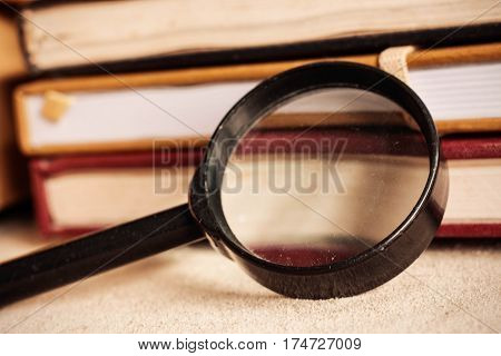 Old magnifying glass of dusty and books on desk.