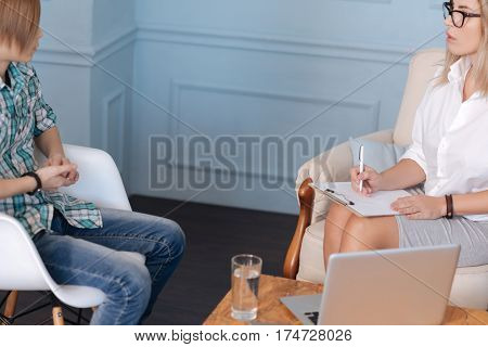 Tell it to me. Composed boy sitting on white chair wearing casual clothes listening to woman