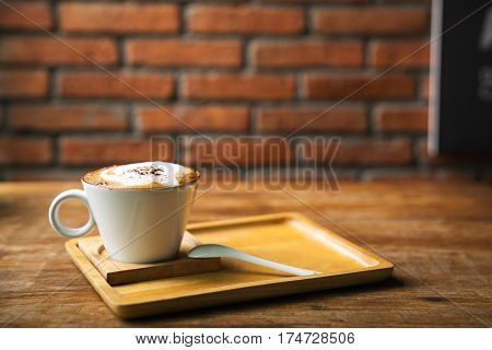 Cup of hot latte art coffee on wooden table. A stylish modern café with wooden tables and a brick wall.