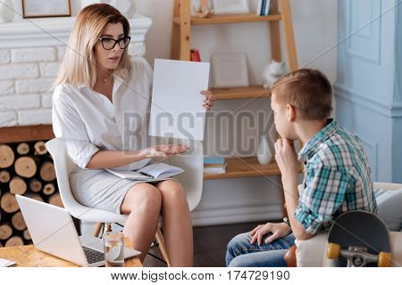 Think about this. Serious psychologist holding notebook on her knees keeping white sheet of paper in left hand while looking on teenager