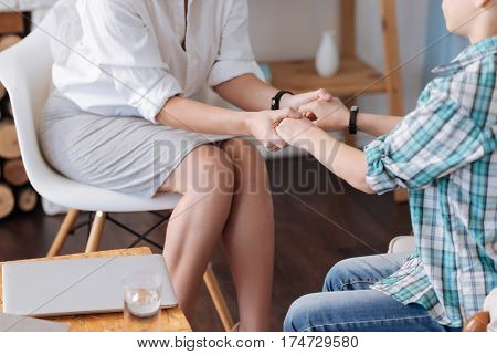Lend credence. Two persons sitting on the chairs having bracelets on wrist while holding tight