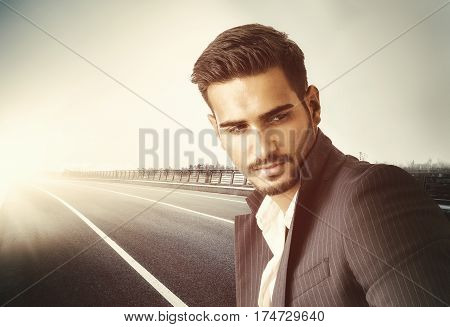 Confident stylish man standing on a roadside and looking away. Horizontal outdoors shot.