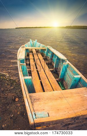 Sunrise on a river with old rustic wooden boat