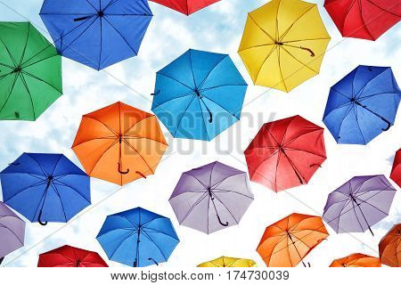 colorful umbrellas hanging against the sky. decorating the city streets