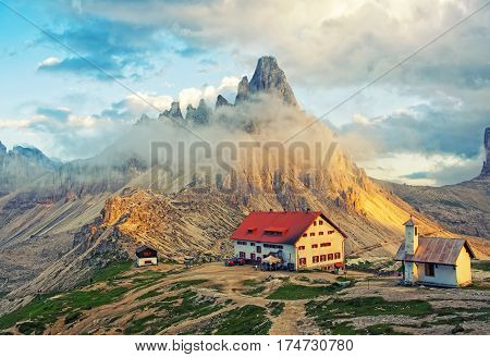 Scenic view of mountain hut and chapel in sunlit with high rocky ridge under cloud on background at sunset. Tre Cime di Lavaredo National Park Dolomites Italy