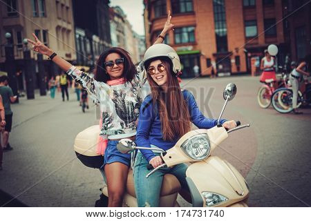 Multi ethnic girls on a scooter in european city.