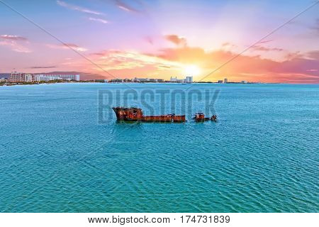 Ship wreck at the coast from Aruba island in the Caribbean Sea at sunset