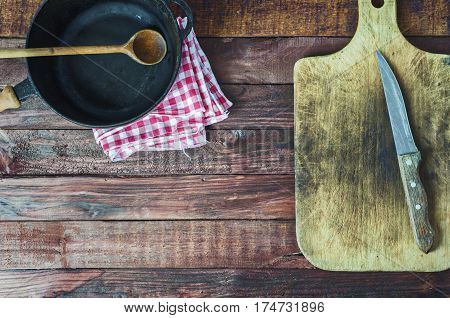 black cast iron pan and cutting board on brown wooden surface top view