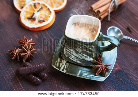 cup of coffee with grief spice star anise and cinnamon on a brown wooden table