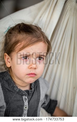 angry little girl closeup , sitting on a fabric hammock