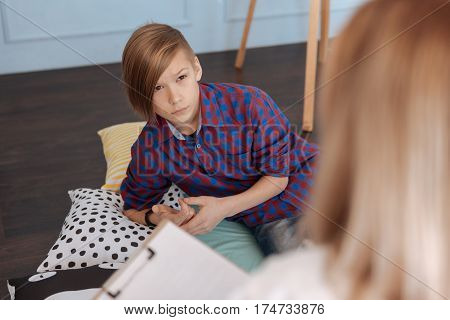 Time for resting. Attentive teenager wearing checked shirt holding hands together while looking at woman
