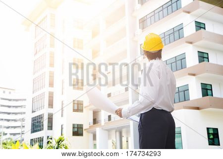 View of an Engineer and worker checking plan on construction site with blur building background.