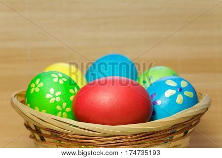 green, yellow, blue  easter eggs in  wooden basket