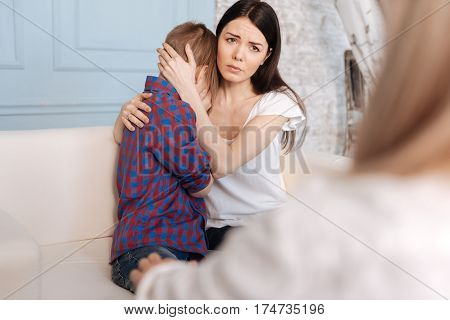 Can you help us. Sad woman hugging her son looking straight sitting on the sofa