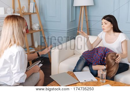 I do not know. Young brunette woman wearing white T-shirt putting her left hand on head of her son while speaking with psychologist