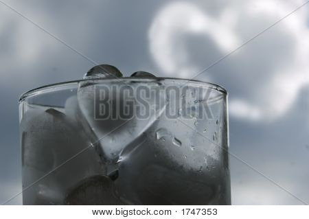 Glass Of Ice Hearts And Heart-Shaped Cloud On Background