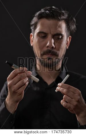 Portrait of man who is decided to quit smoking cigarette in favor of electronic cigarette.