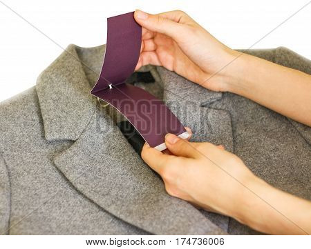 Clothes, Wear And Fashion Concept - Close Up Of Hand Holding Price Tag Of Grey Wool Coat.