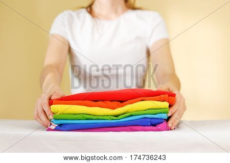 Girl Hold On A Stack Of Ironed Colored Linen. Pile Of Clothes. Ironing Concept. All Colors Of The Ra