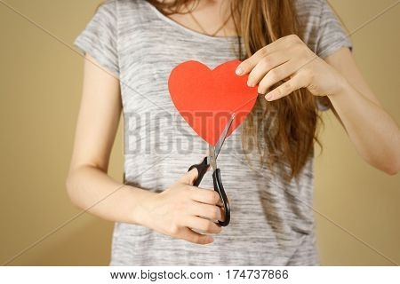Female Hand Holding Red Valentines Card With Heart On Isolated Background. Сut With Scissors.