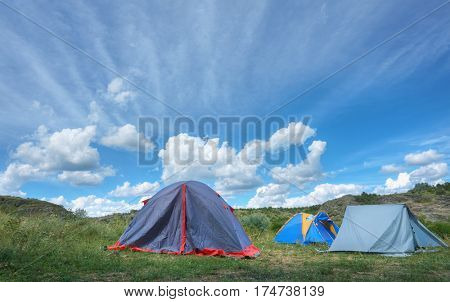 Summer landscape with tents on meadow