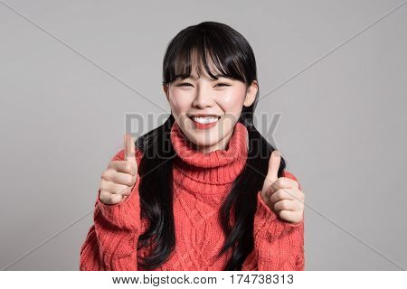 Studio portrait of twenties Asian woman of happy appearance holding thumb up