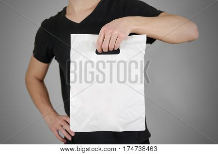 Man shows blank plastic bag mock up isolated. Empty white polyethylene package mockup. Consumer pack ready for logo design or identity presentation. Commercial product food packet handle.