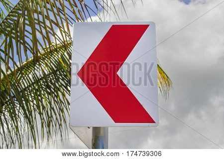Red arrow pointer on tropical background. Roadside with palm tree leaves and cloudy sky. Road turn sign. Summer holiday travel concept. Serpentine way attention sign. Highway turn. Safe drive image