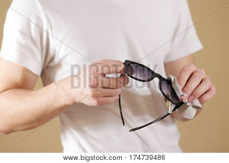 Man In White T Shirt Hand Cleaning Black Sun Glasses Lens With Isolated Background