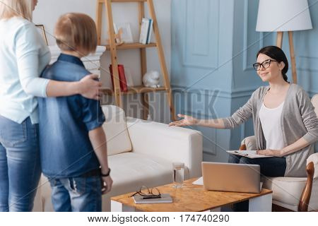 Take sits. Positive delighted professional wearing casual clothes holding folder on her knees while keeping her arm in the air